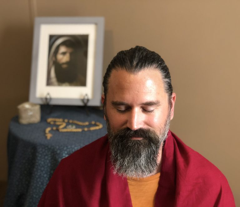 Man sitting and meditating with a rosary and an image of Christ in the background